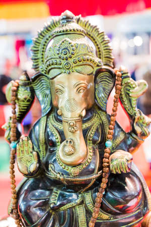 Golden statue of the goddess Ganesh. Bench oriental objects. Selective focus.