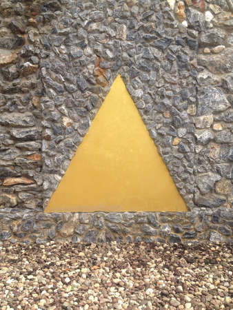 gold: Gold triangle on stone wall Stock Photo