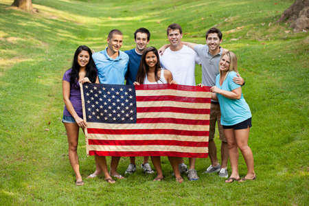 hispanic americans: Diverse group of young people holding an American flag Stock Photo