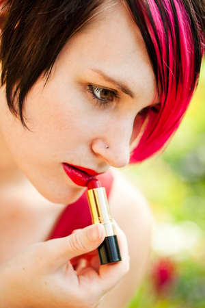 Young punk woman putting on lipstick in the garden photo