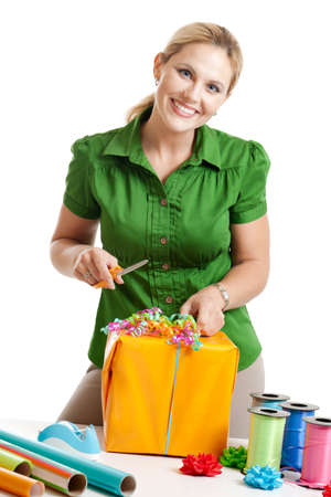 Woman wrapping a gift isolated on white photo