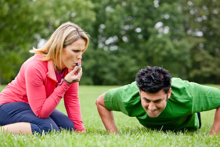 Female coaching blowing whistle at athlete doing push ups Banque d'images