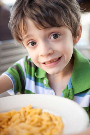 7 year old boys: Child eating macaroni and cheese Stock Photo