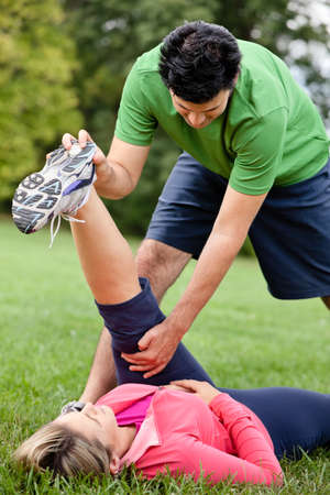 Fitness trainer stretching womans leg