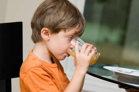 Child drinking orange juice at the breakfast table