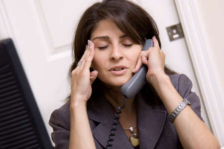 Businesswoman in home office with a headache
