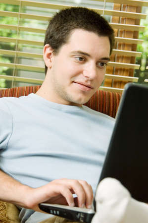 Teen boy at home on laptop photo