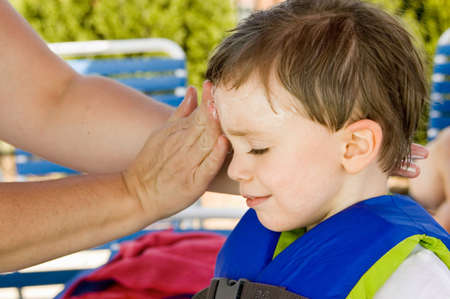 safety jacket: Child getting sunscreen application