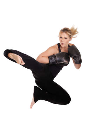 Female kickboxer performing flying side kick photo