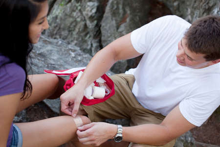 first aid: Man applying first aid to woman