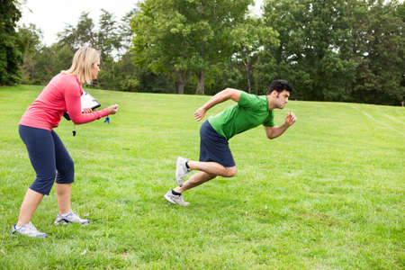 Athlete with fitness coach sprinting  Banque d'images