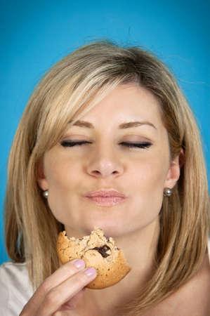 Woman enjoying chocolate chip cookie photo