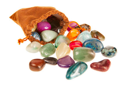 Bag of colorful stones isolated on white photo
