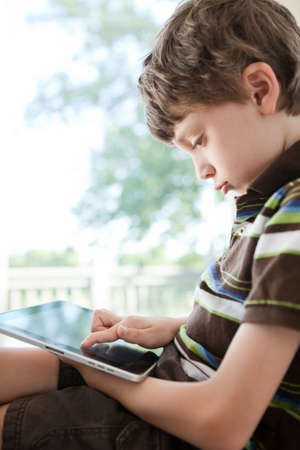 Child playing on digital tablet photo