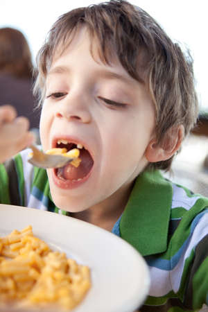 7 years old: Child eating macaroni and cheese Stock Photo