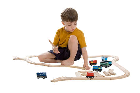 Child playing with wooden train set isolated on a white background photo