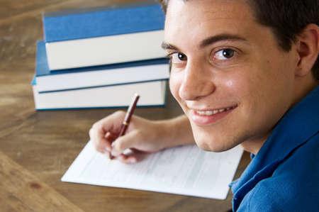 十代の少年が大学アプリケーションの記入 写真素材