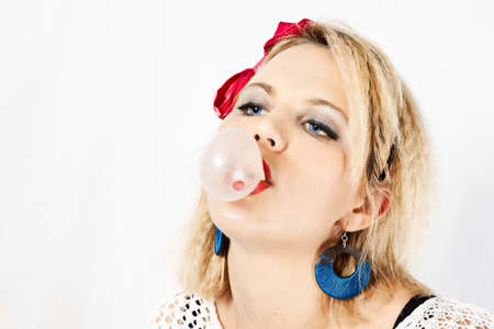 Woman dressed in 1980s attire blowing bubble gum photo