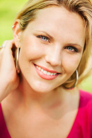 smile close up: Beautiful blond woman sweeping back hair portrait Stock Photo