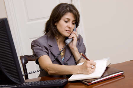 Business woman working in home office on the phone taking notes photo