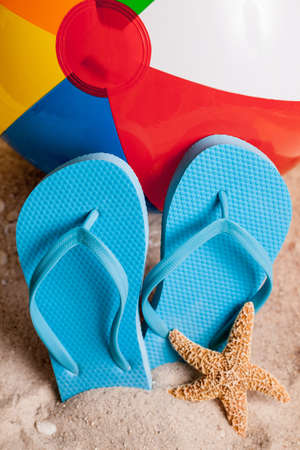 Flip flops and beach ball in the sand photo