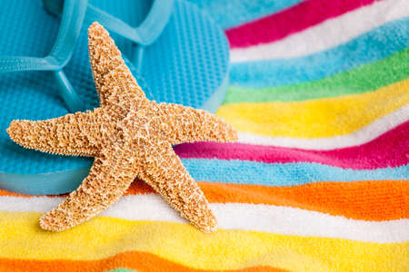 Starfish and beach shoes on a beach towel