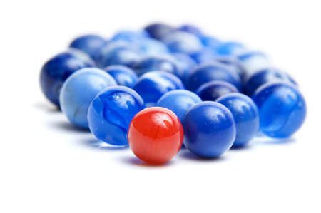 one of a kind: Red vintage marble leading blue marbles isolated on white