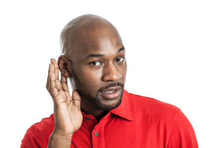 cupping: Portrait of a handsome excited black man in his late 20s cupping ear listening isolated on white