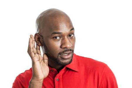 personas escuchando: Retrato de un hombre negro guapo emocionado en sus �ltimos 20 a�os de cataci�n o�do atento aislado en blanco Foto de archivo
