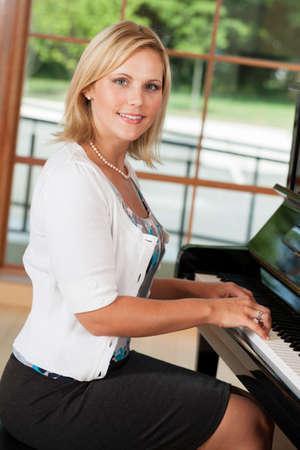 tocando piano: Mujer de mediana edad tocando el piano