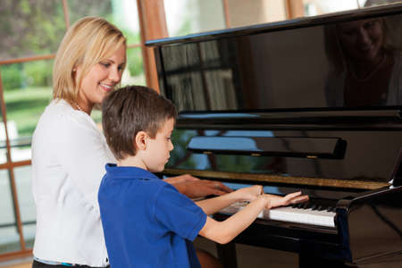 Piano teacher giving lessons to an 8 year old boy photo