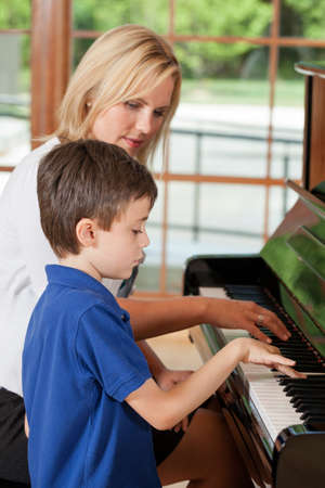 Piano teacher giving lessons to an 8 year old boy
