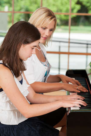 Piano teacher giving lessons to a tween girl student photo