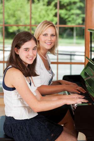 teaching music: Piano teacher and tween girl student sitting at the piano