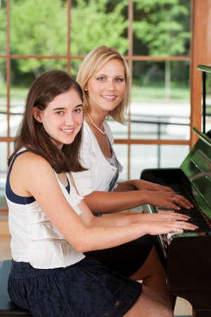 Pianoleraar en meisje tussen student zit aan de piano Stockfoto - 22086424