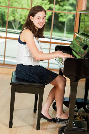 Meisje tussen piano student zitten aan een piano