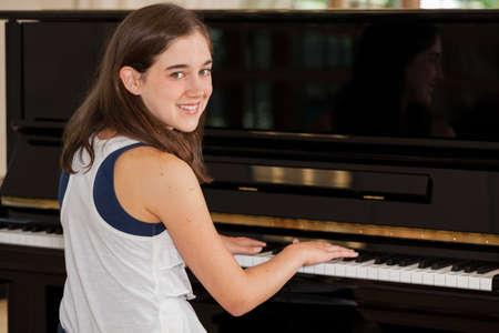 トゥイーンの女の子ピアノ学生はピアノで座っています。