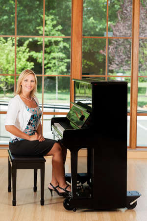 upright piano: Piano teacher sitting at an upright piano Stock Photo