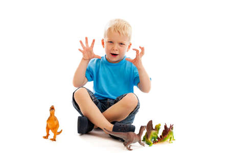 growling: 3 year old boy playing with toy dinosaurs isolated on white Stock Photo