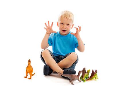 juguetes antiguos: Niño de 3 años jugando con los dinosaurios de juguete aislados en blanco