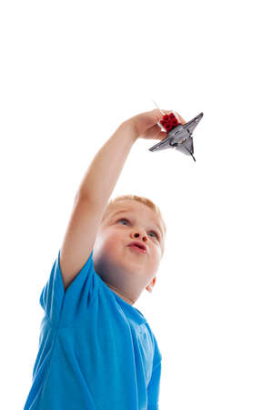3 year old boy playing with space shuttle toy isolated on white