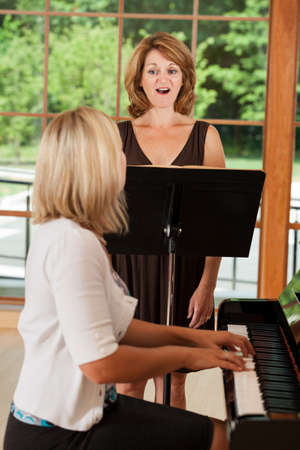 adult learning: Mature woman taking singing voice lessons with teacher at the piano
