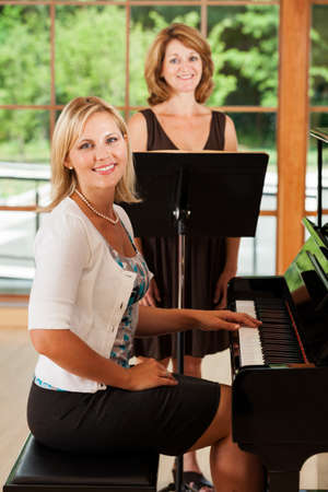 Mature woman taking singing voice lessons with teacher at the piano photo