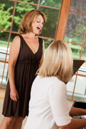 Rijpe vrouw die zangstem lessen met leraar aan de piano