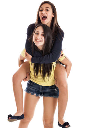 pre adolescence: Happy tween and teen sisters on piggyback isolated on a white background