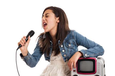 pre adolescence: Tween girl singing with karaoke machine isolated on white Stock Photo