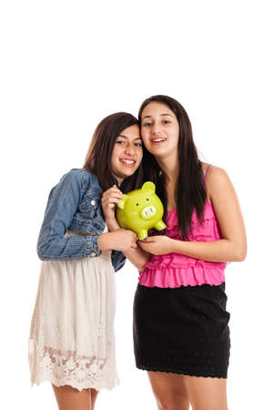 13: Teen and tween sisters holding a piggy bank isolated on white