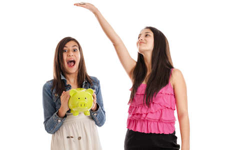pre teens: Tween and teen sisters dropping change from a piggy bank isolated on white