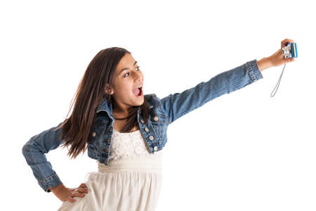 pre adolescence: Tween girl taking self portrait with digital camera isolated on white