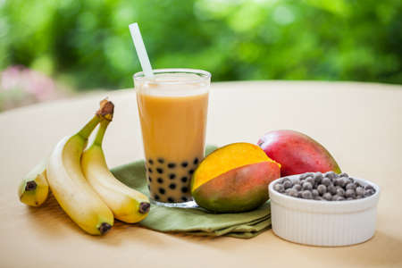 banana leaf: Mango smoothie bubble tea with fruit and tapioca pearls in the garden